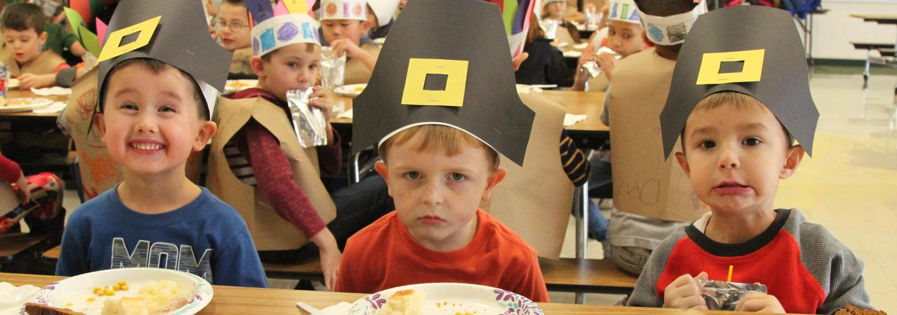 Students wearing Pilgrim hats they have made have Thanksgiving feast.