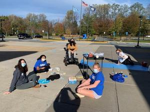 photo of leadership students painting welcome signs with chalk