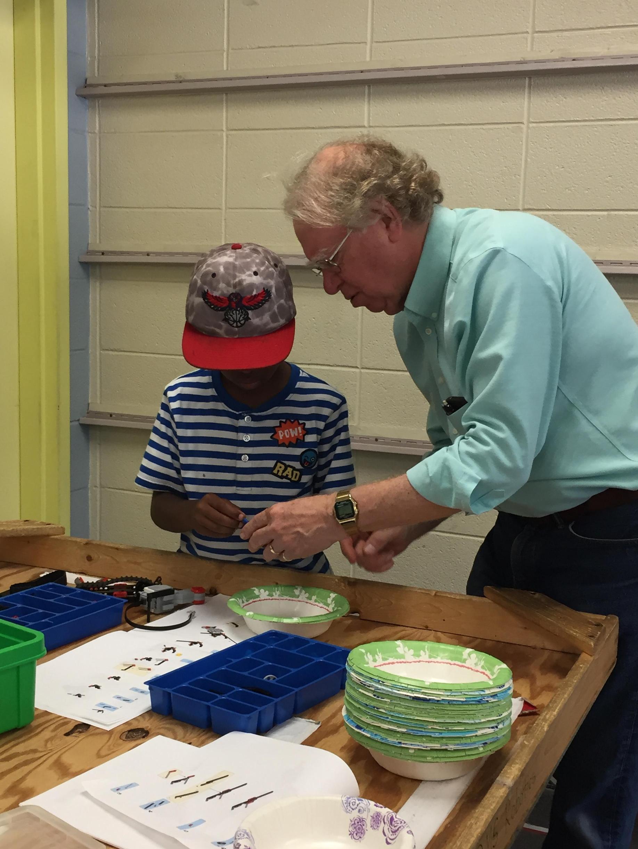 Child getting help with robotics activity