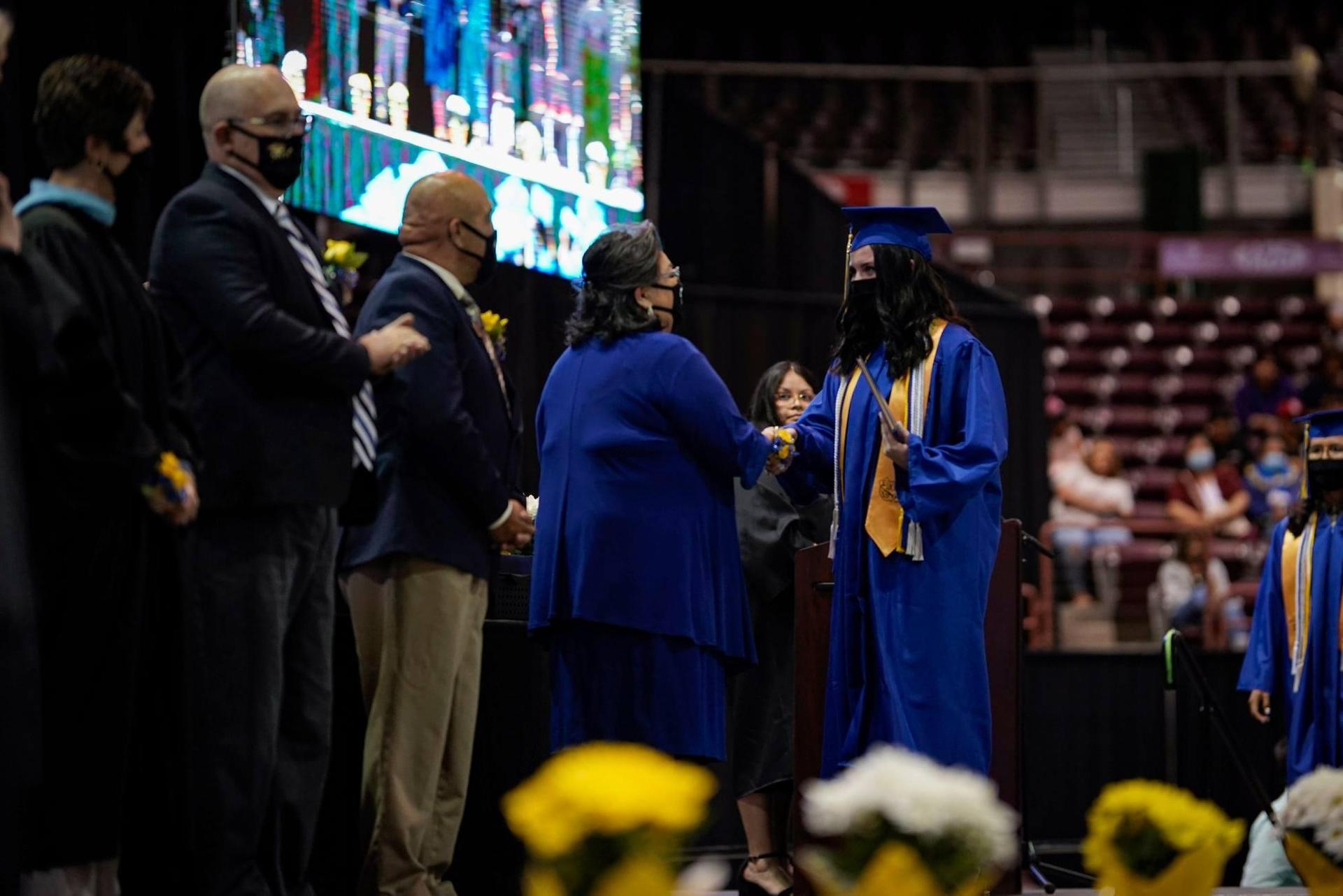 Marisela handing diploma to graduate