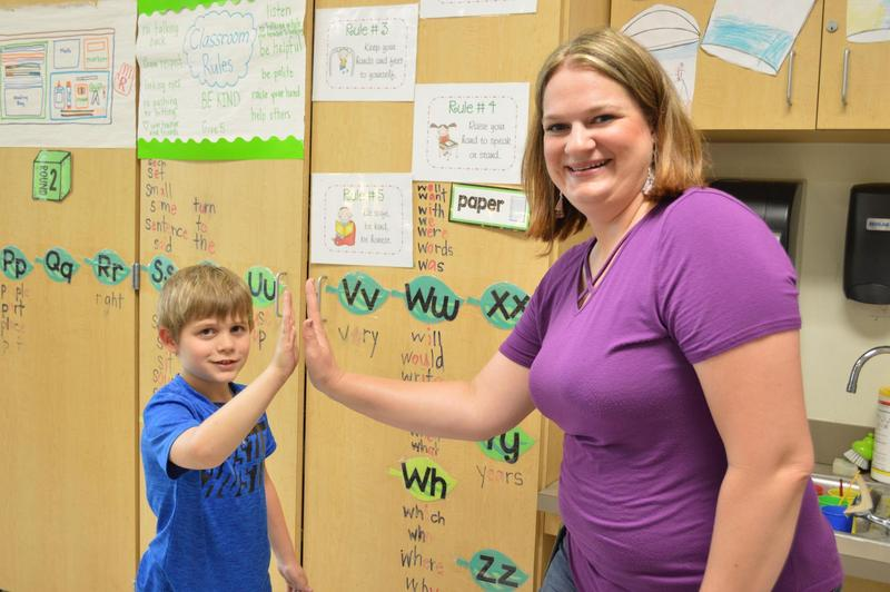 kid and teacher high fiving