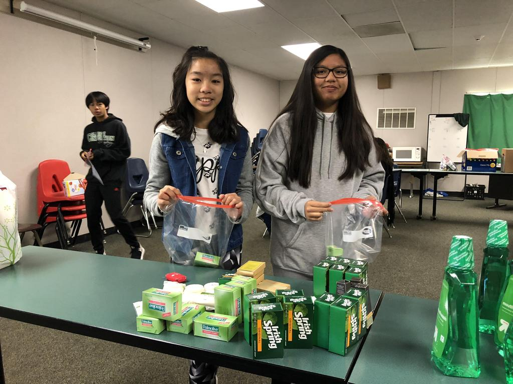 Two CCA students putting toiletries into a bag.
