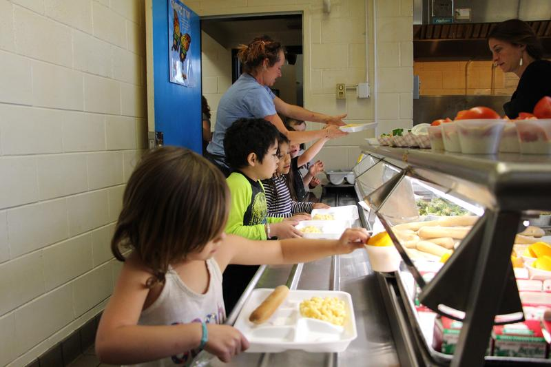 Students picking food items in line at cafeteria.