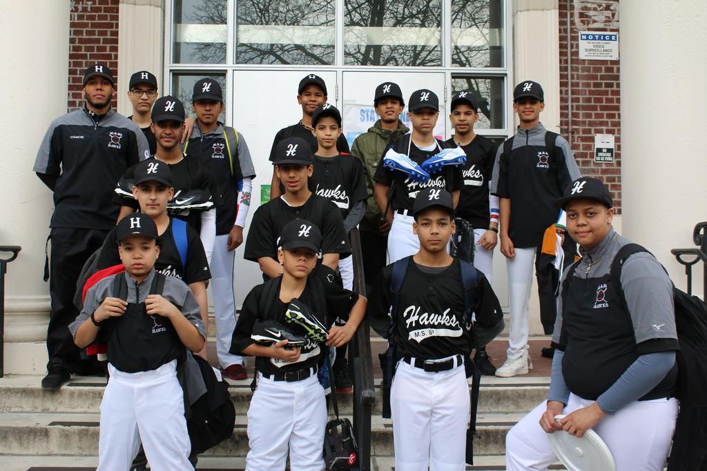 boys baseball team posing in front of the school