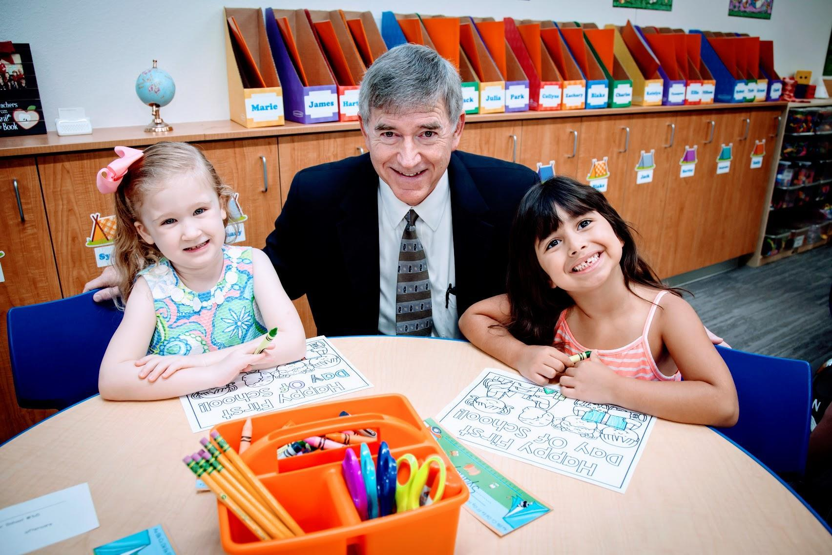 Dr. Trigg smiling with two elementary students at a round learning table