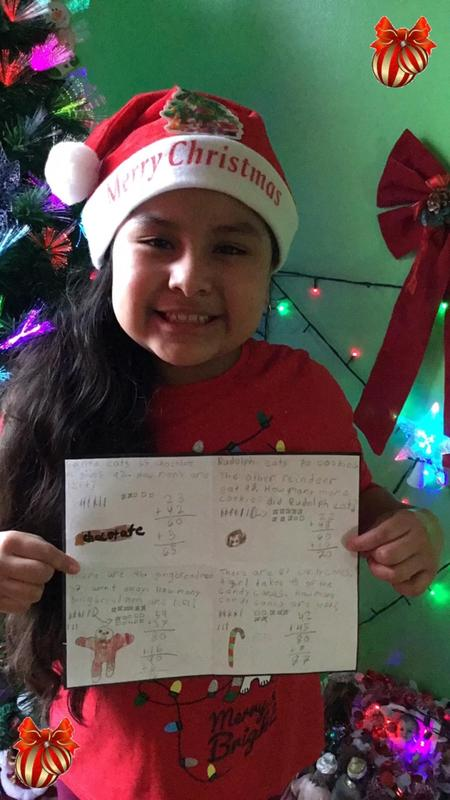 Girl wearing Santa hat and holding math work