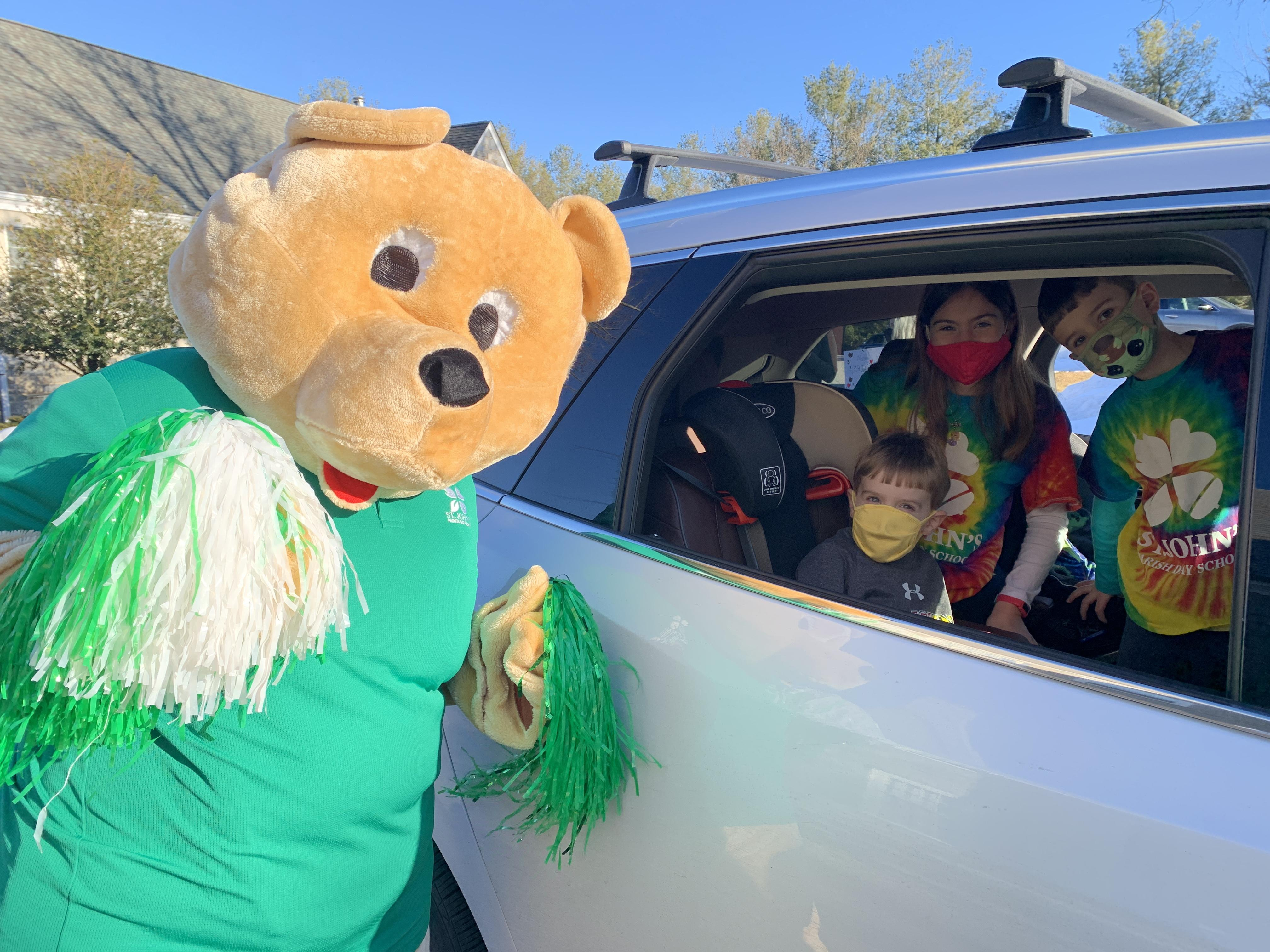 students posing for a picture with spirit bear mascot from inside their car