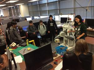 students gathered in a group watching a presenter who is standing next to a robot