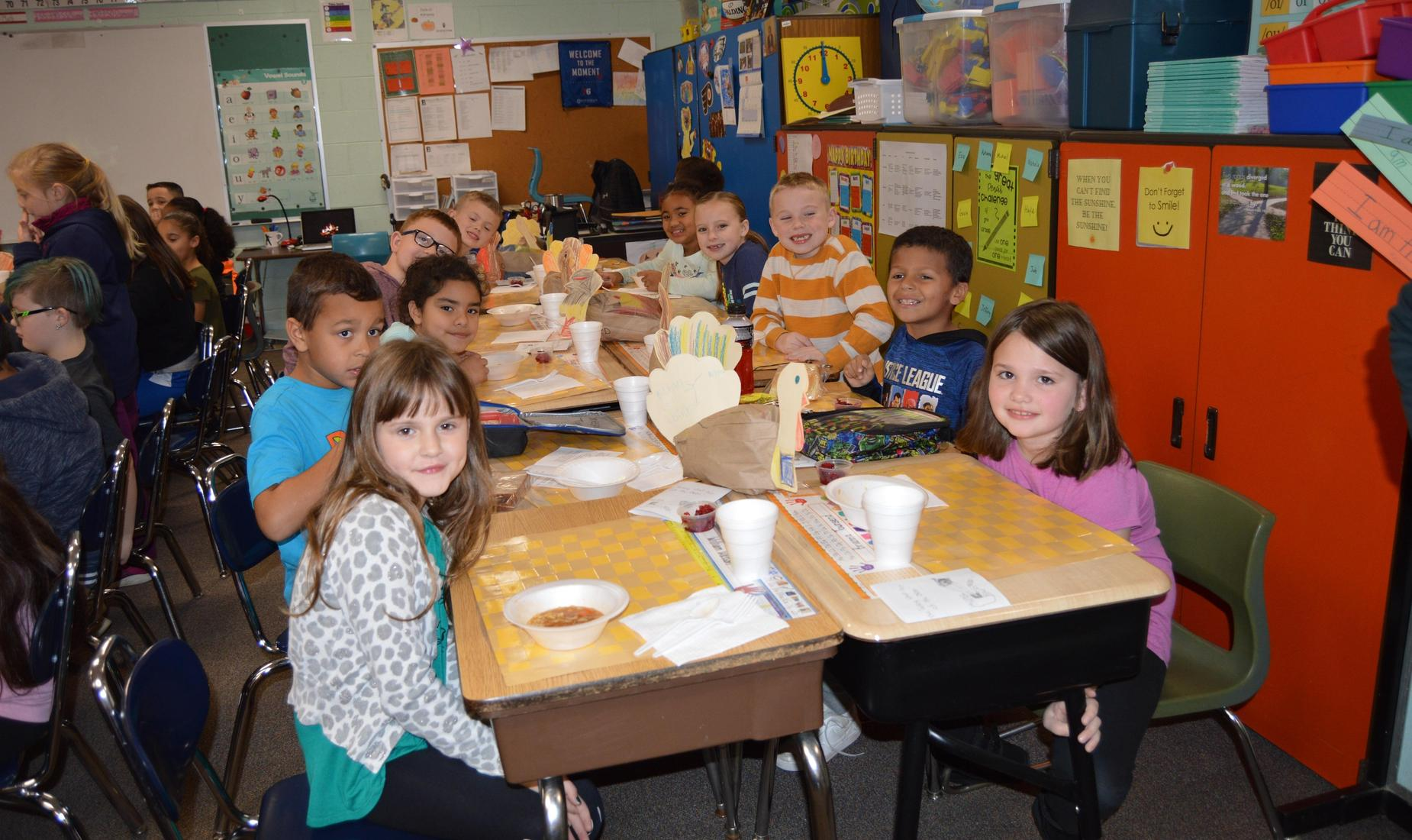 Boys and girls in 2nd grade sitting at their desks waiting for their Thanksgiving Feast.