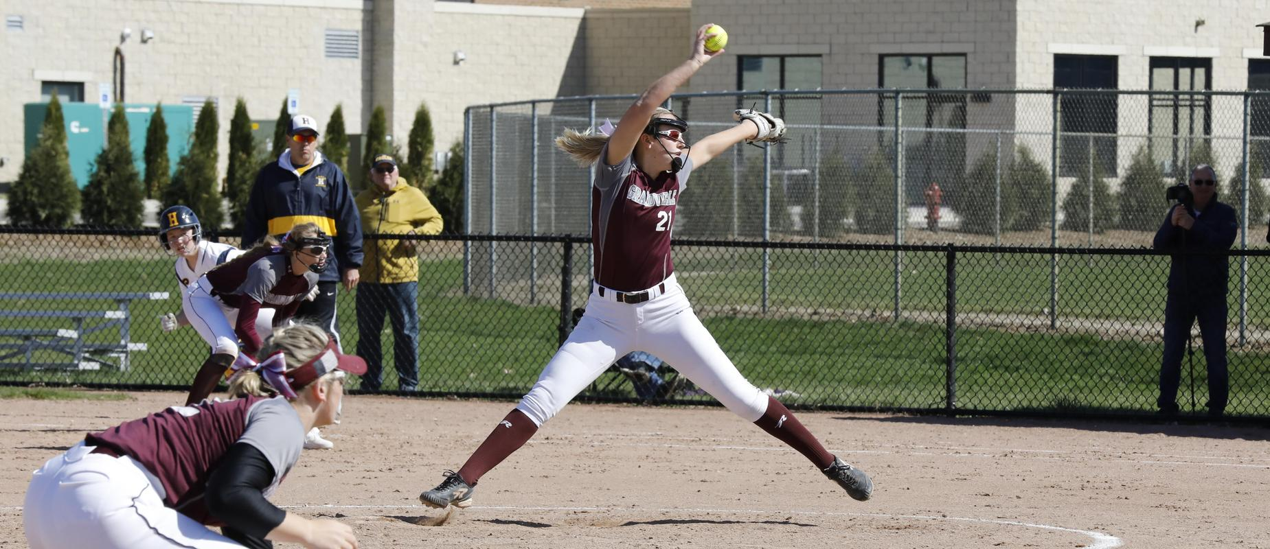 girl in maroon uniform pitches ball on diamond