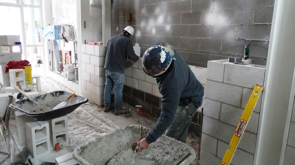 Two masons are pictured October 3, 2019 constructing a concrete block wall at the construction side of the soon to be completed main pedestrian entrance at Beekmantown Elementary School.