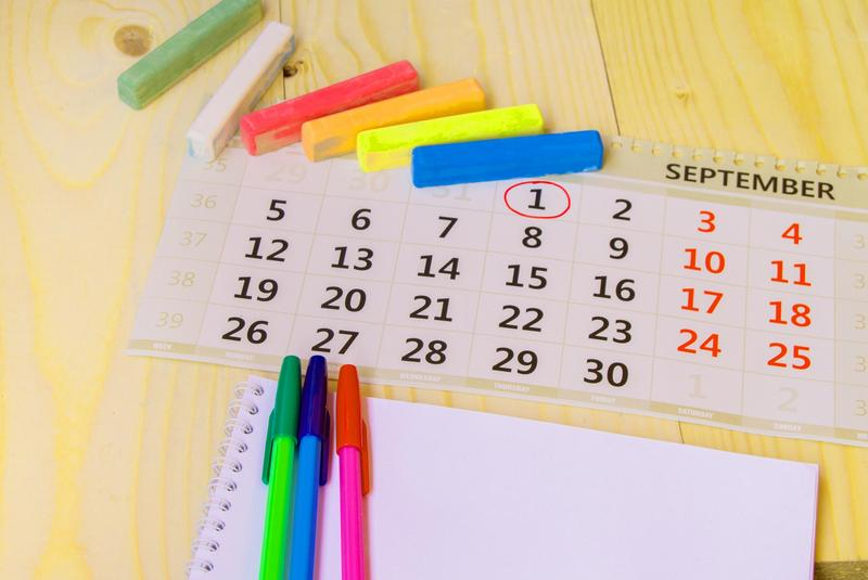 A calendar with markers and pens around it.