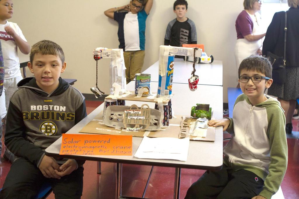 Two students sit next to their STEM projects inside the Webster School cafeteria