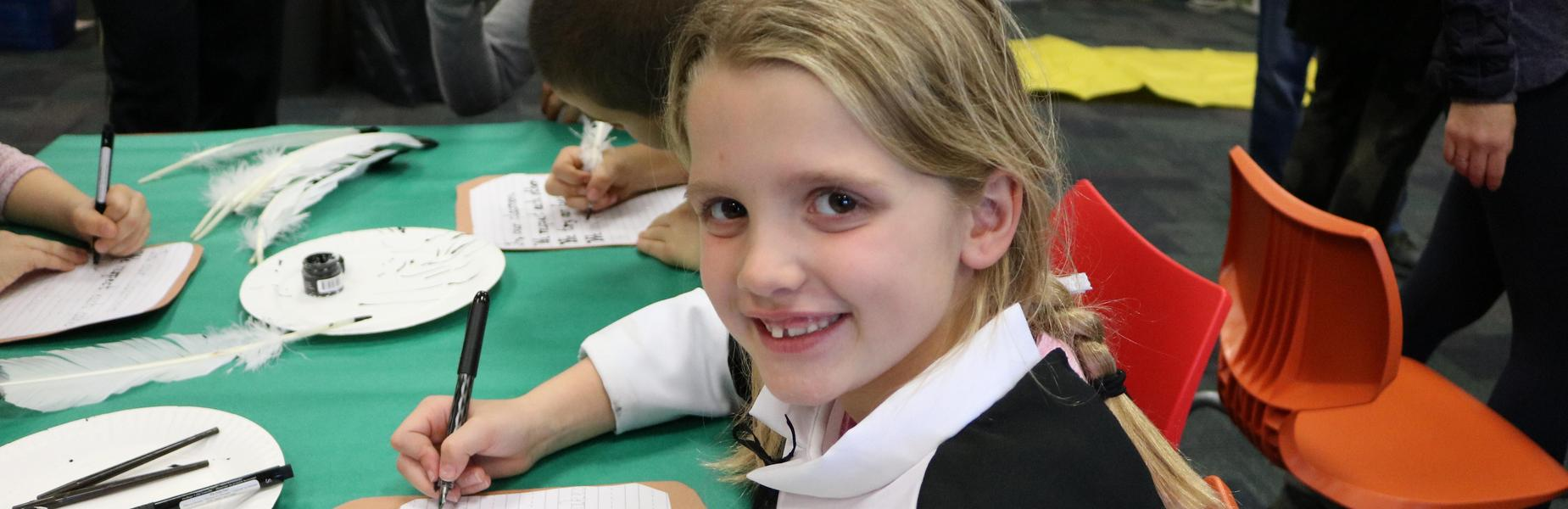 2nd grader at Wilson dresses in colonial era dress and tries her hand at calligraphy as part of Colonial Days.
