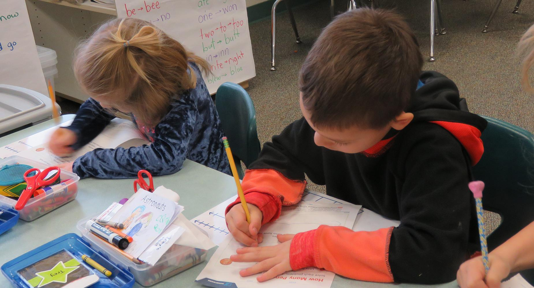 Two children work on a math worksheet with pencils and papers.