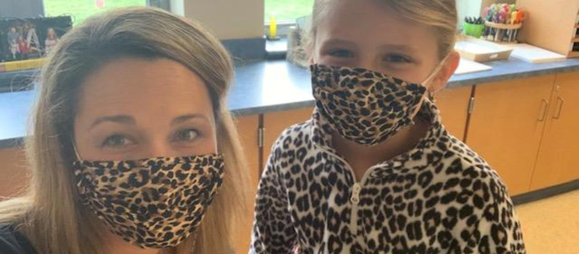 teacher and student wearing matching leopard masks