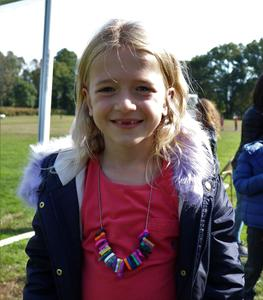 2nd grader shows off her charm necklace she earned as a runner in the Mileage Club at recess.