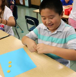 Photo of: Tamaques 3rd grader Jerry Han enjoys using wax sticky twists as students in Cathy Chao's class reinforce what they've learned about rounding to the nearest 10 or nearest 100.