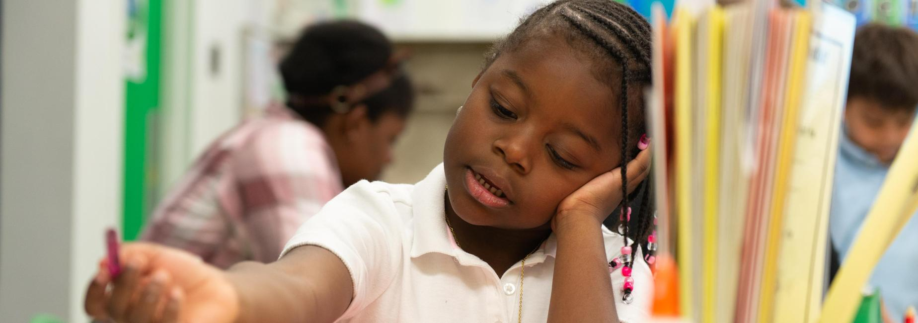 An elementary school student writing at a table, leaning her head against her hand.