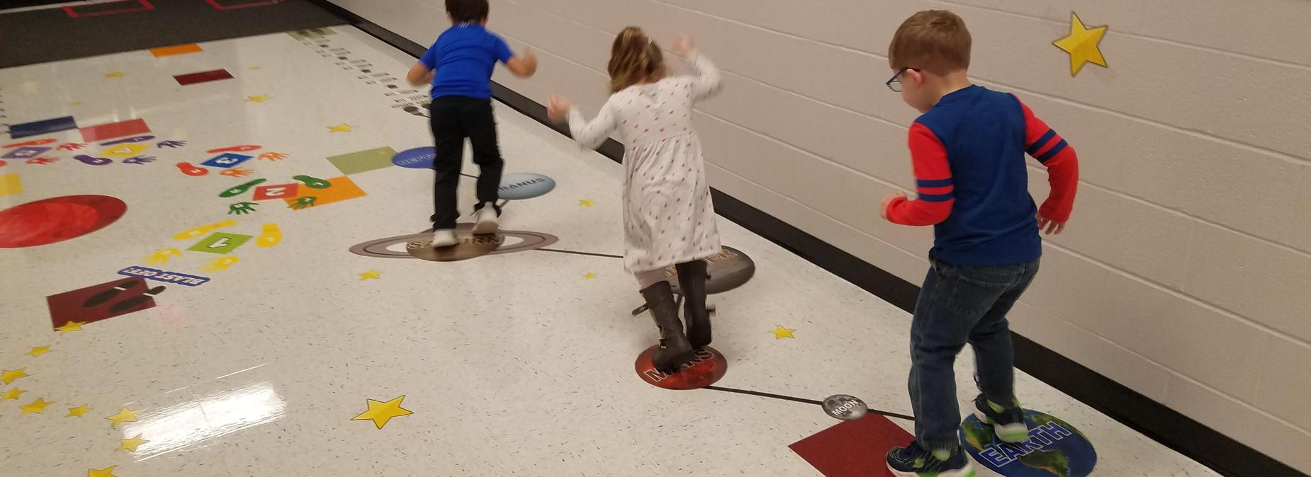 Kids jumping on solar system mats