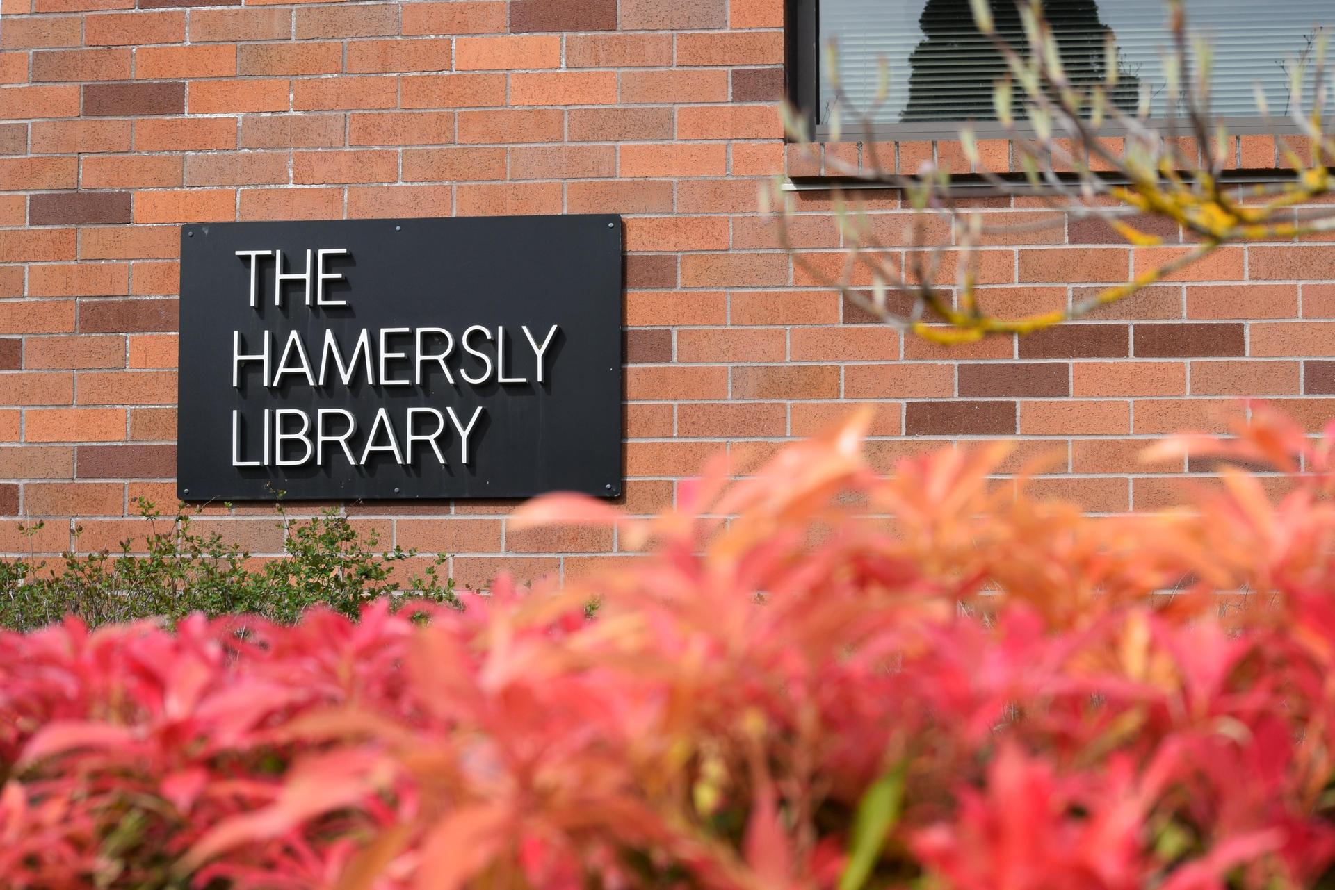 exterior of hamersly library, a brick building, with red foliage in foreground