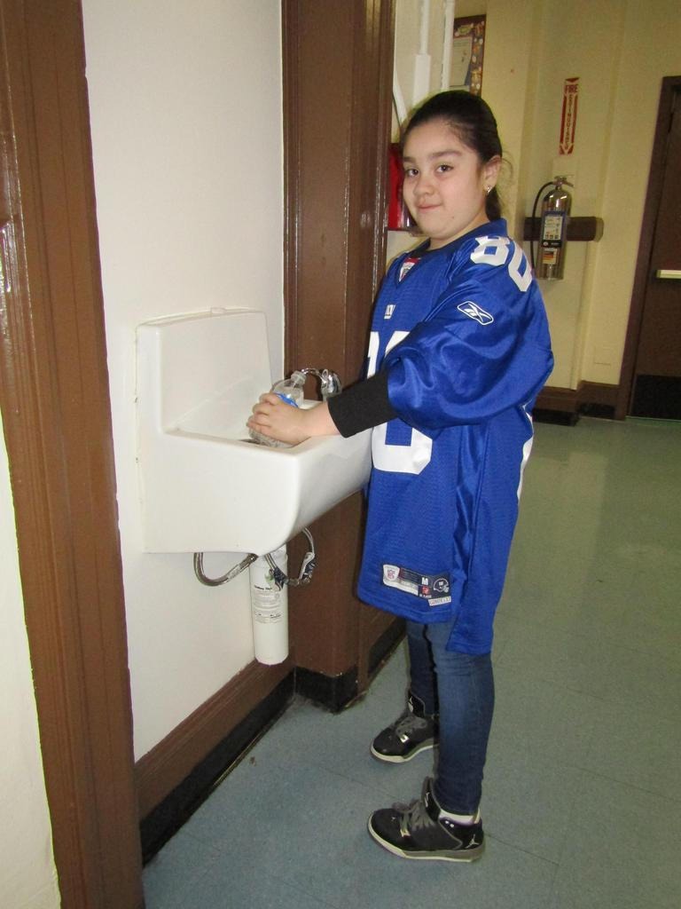 girl wearing a giants jersey filling up a water bottle