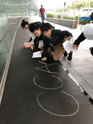 "Students using chalk to write ""CCA."""