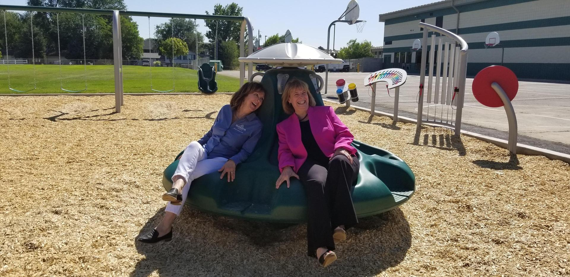 Superintendent Paula Kellerer and Mayor Debbie Kling take a spin on the merry-go-round at Iowa Elementary School.