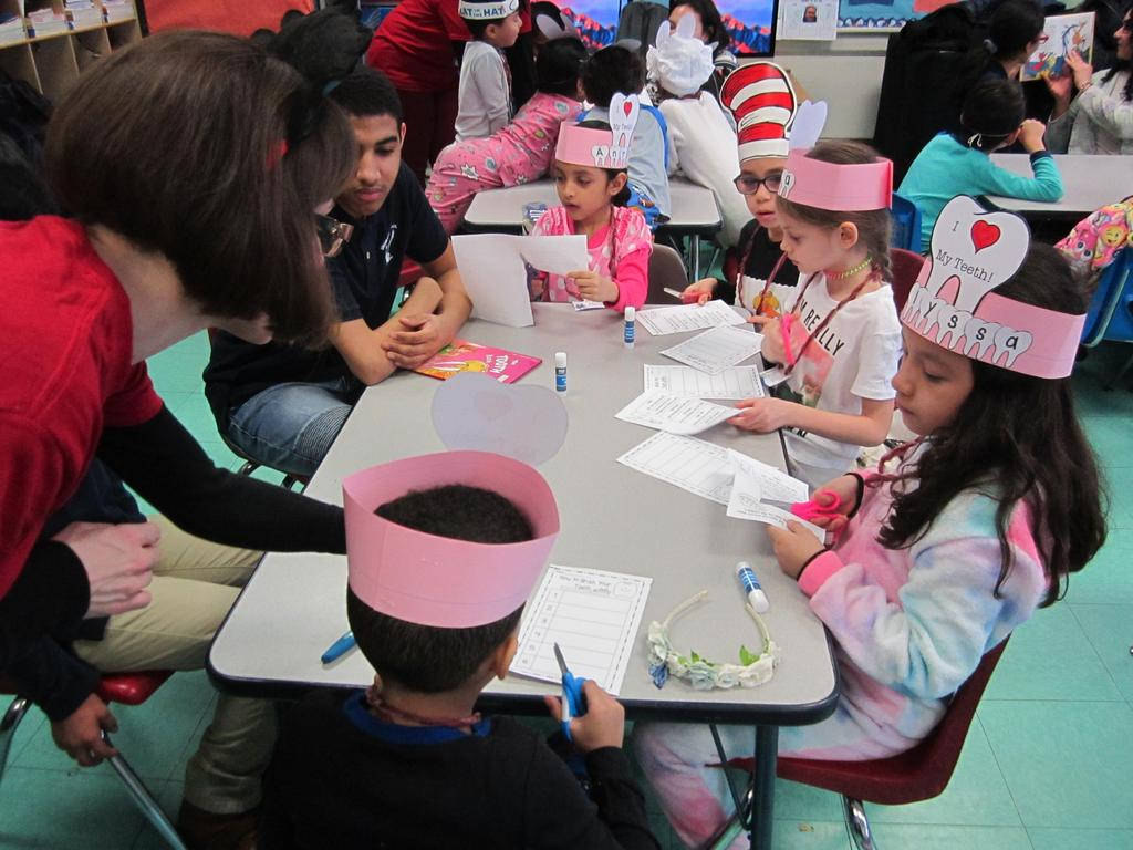 parent volunteer helping a group of children cutting out paper for an activity