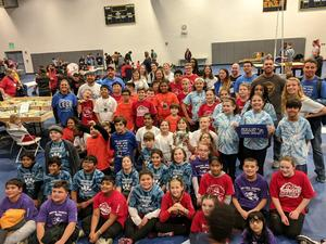 Large group of LEGO League team members and their coaches and parent helpers wearing their team shirt. Some are red, purple, orange, blue tye dye and white tye dye