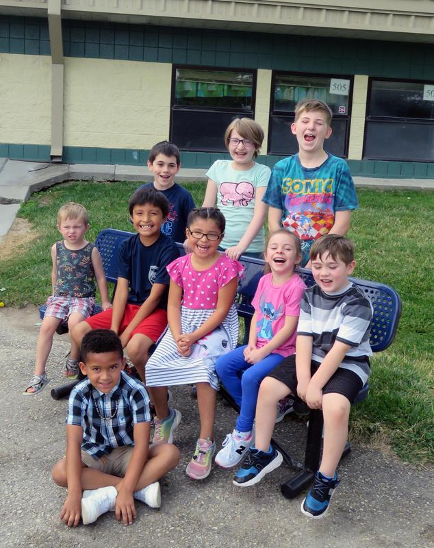 Elementary school children gather around a Buddy Bench and laugh.