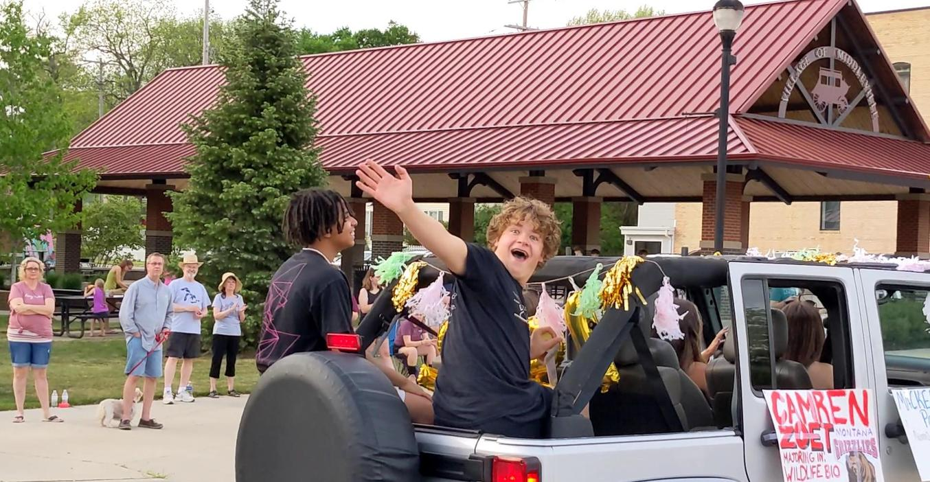 Cam Zoet waves to friends during the senior cruise.