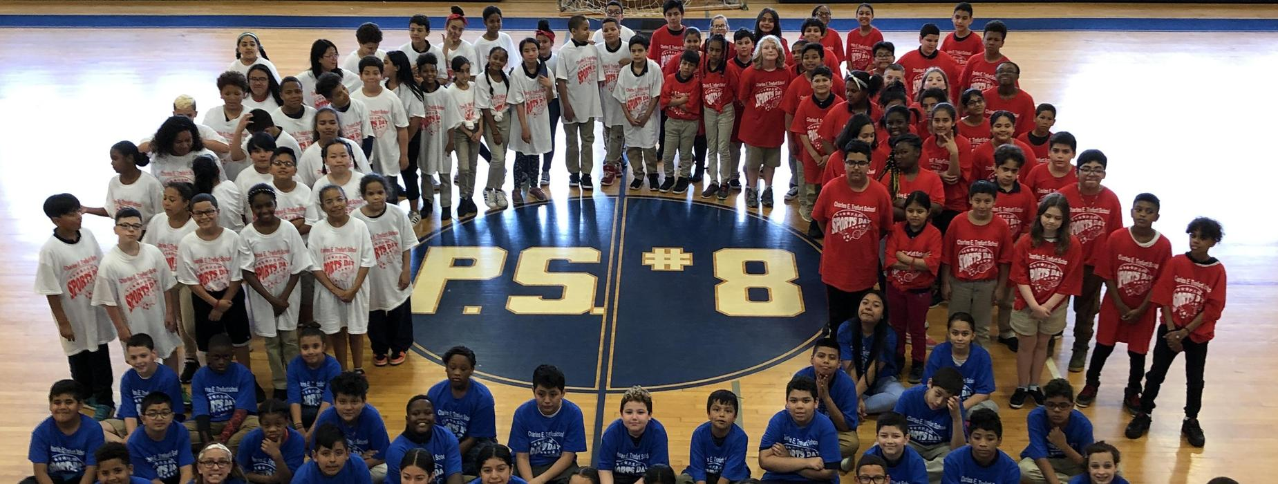 A large group of PS8 students stand around a PS8 sign in the school gymnasium wearing