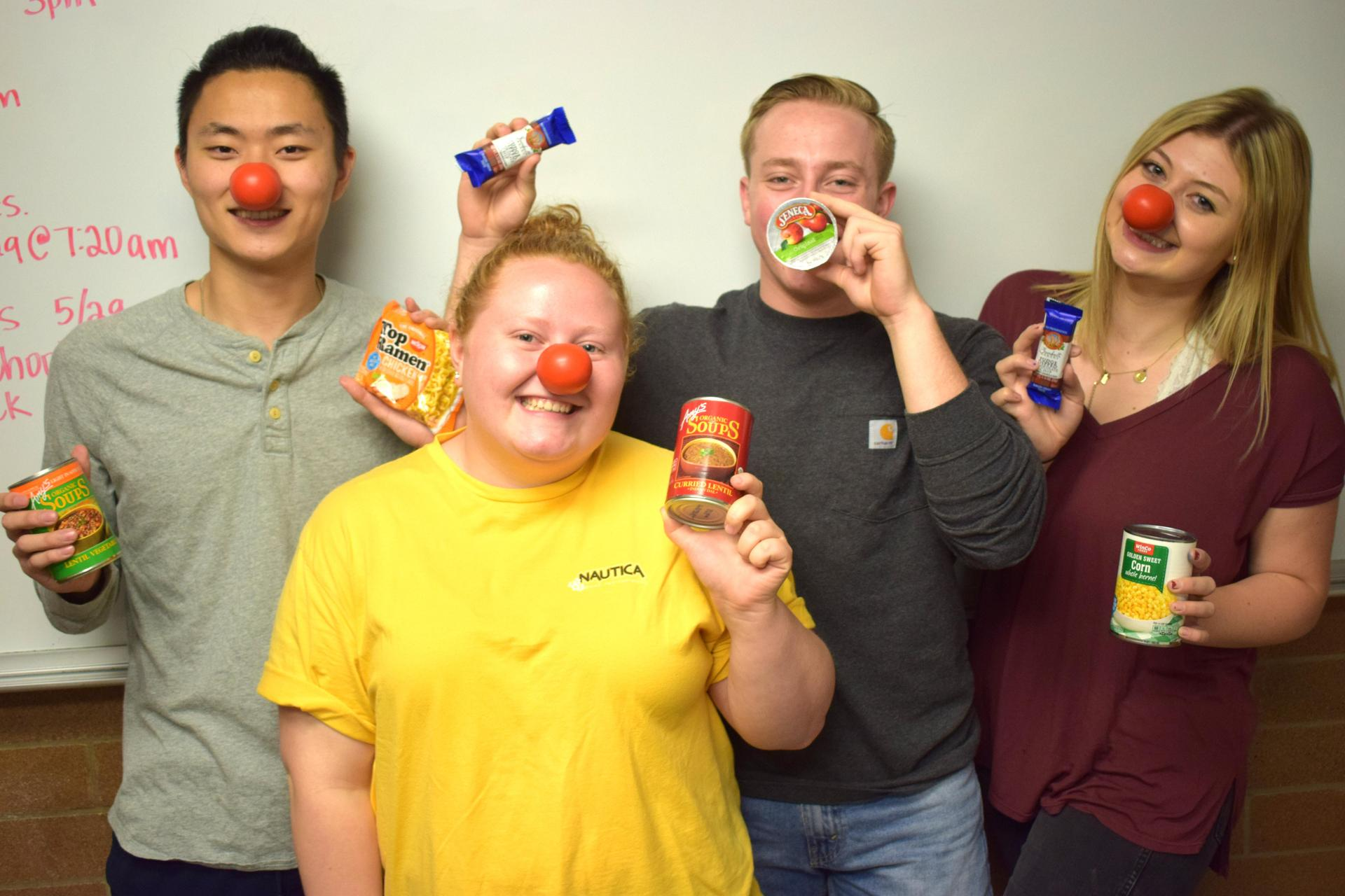 students posing with foods needed for food drive