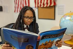 Picture of Student reading a textbook.