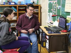 :  McKinley School teacher Joseph Paradise guides his 5th graders during an online video chat with a class in Atlanta, Georgia, encouraging them to share predictions, questions, and observations about the novel both classes are reading.