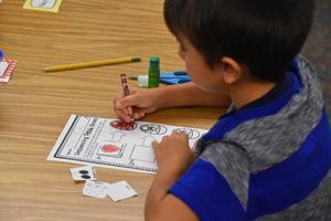 New kindergarten student working on a handout.