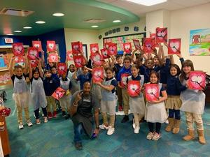 group photo of the students and the artist holding up their heart painting