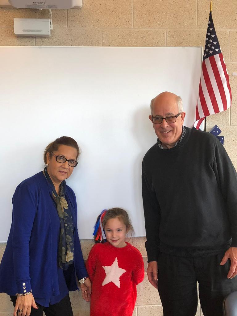little girl proudly stands with her veteran grandfather & grandmother