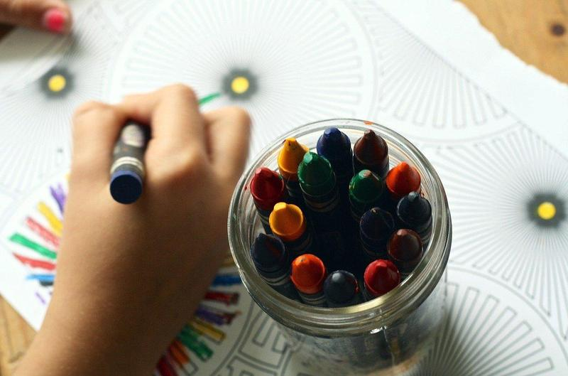Close up of child's hand drawing with crayon.