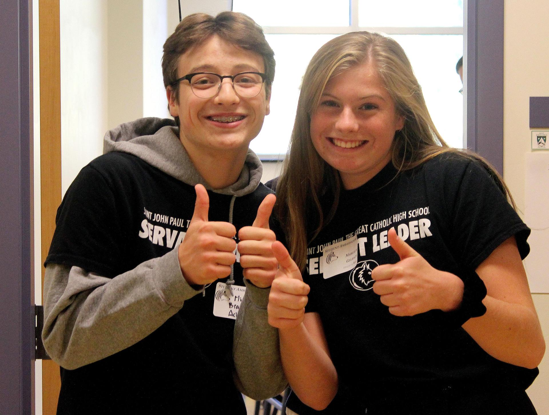 Two servant leaders give a thumbs up to welcome visitors