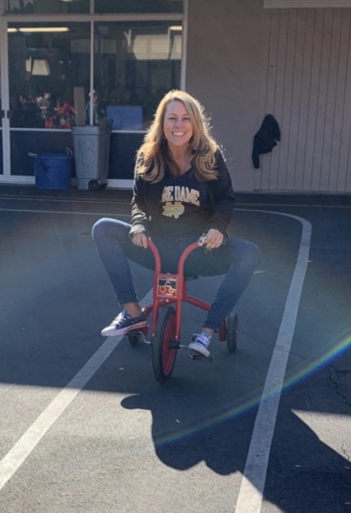 Principal Ms. Holm riding a tricycle