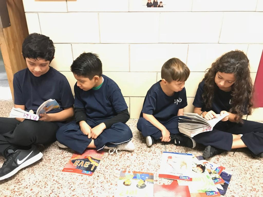 Students reading books in the hallway