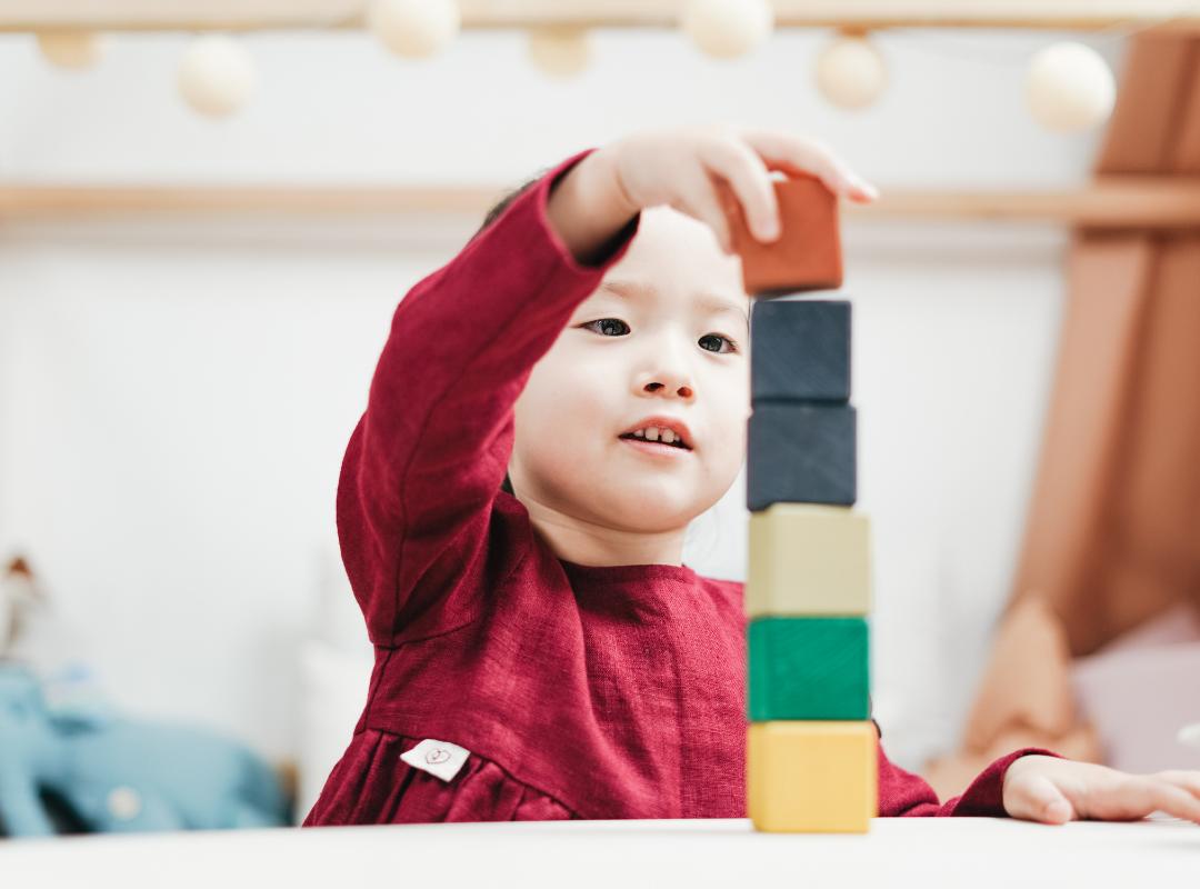 child putting blocks in stack