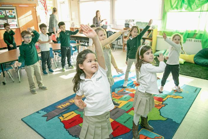 Students at HudsonWay Immersion School stretch their legs in a Brain Break