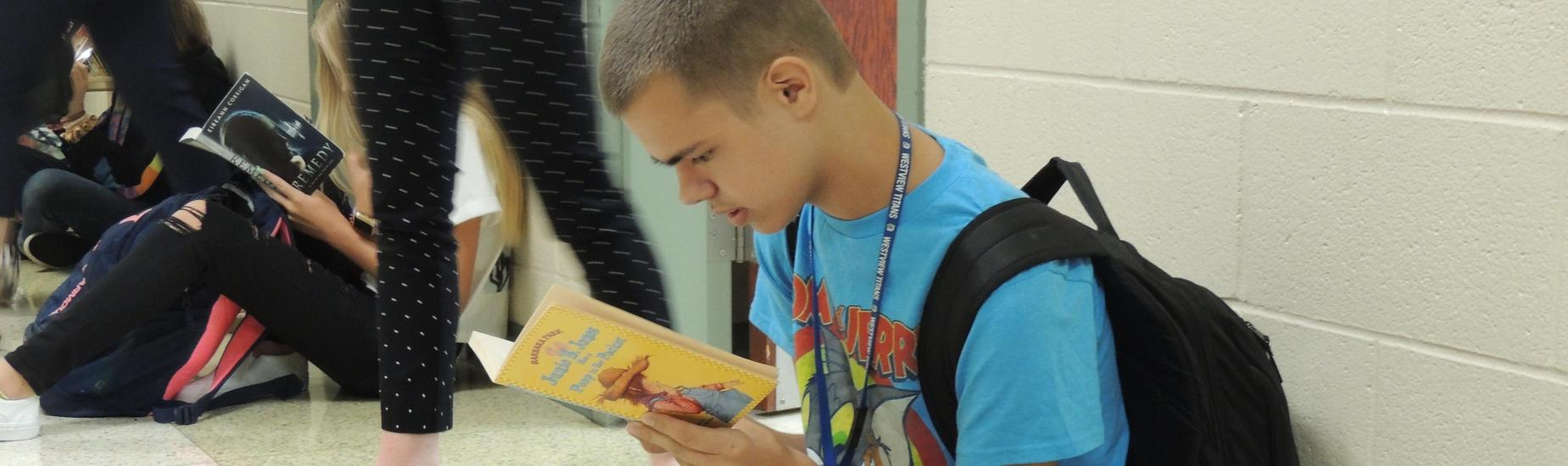 8th grade student reading in the hallway