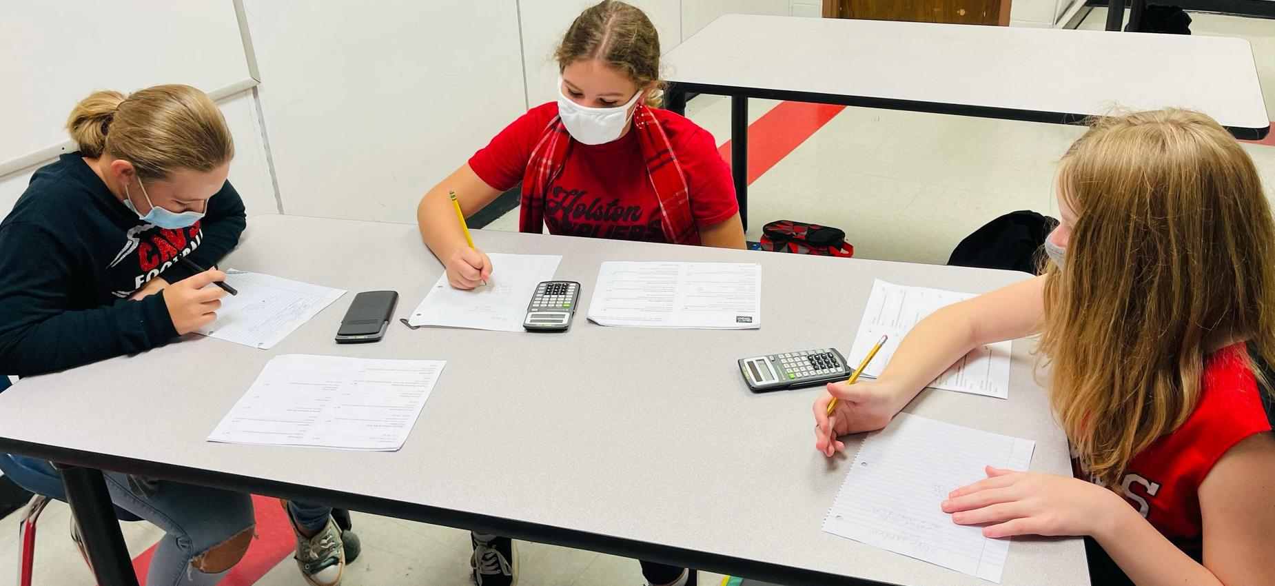 Three students work on math in a classroom.