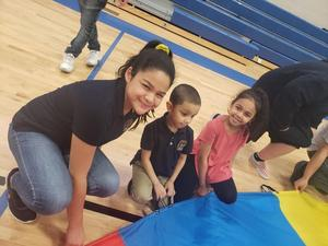 two small kids kneeling on gym floor with older girl