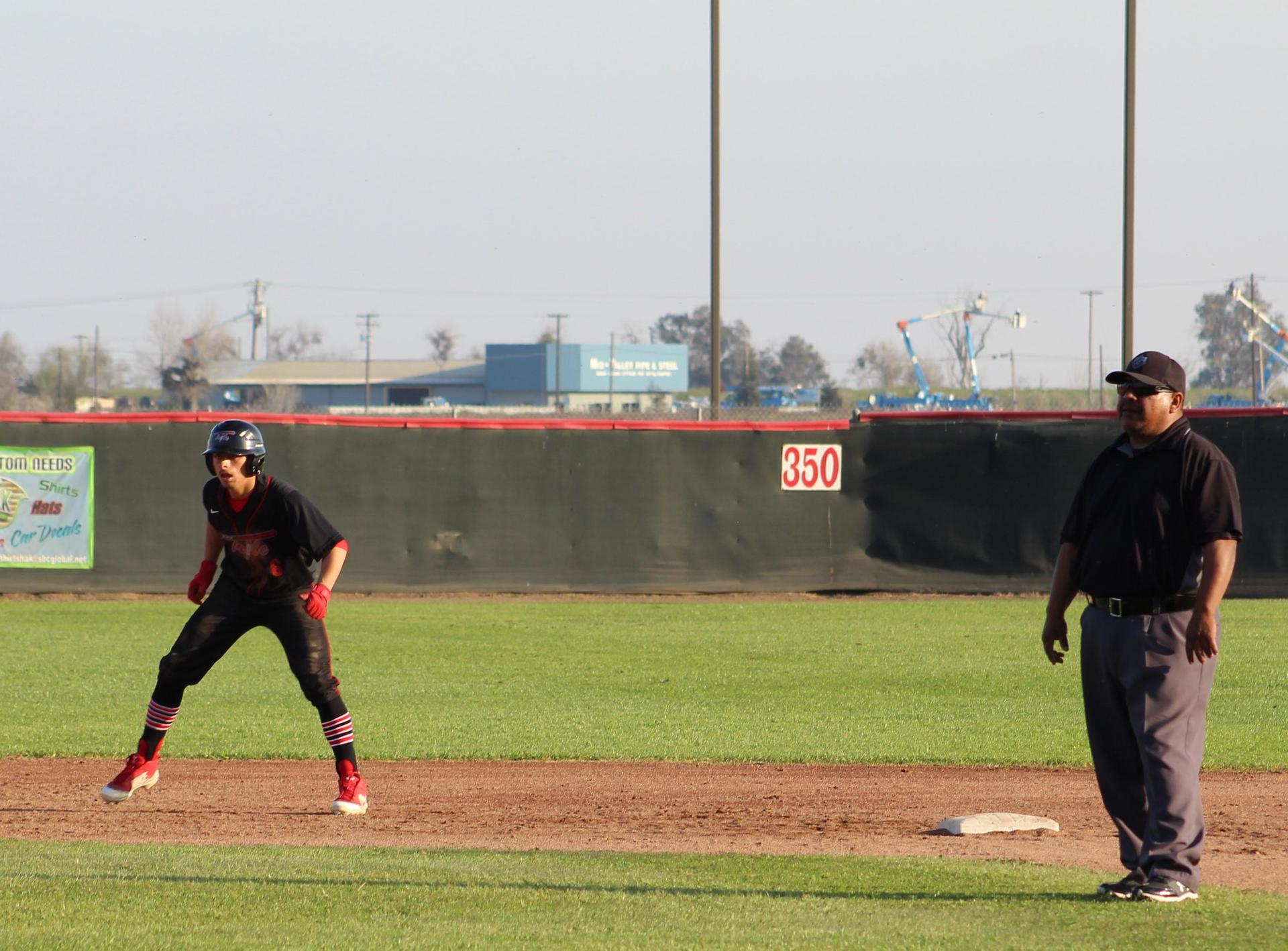 varsity baseball players in action against Sierra Pacific
