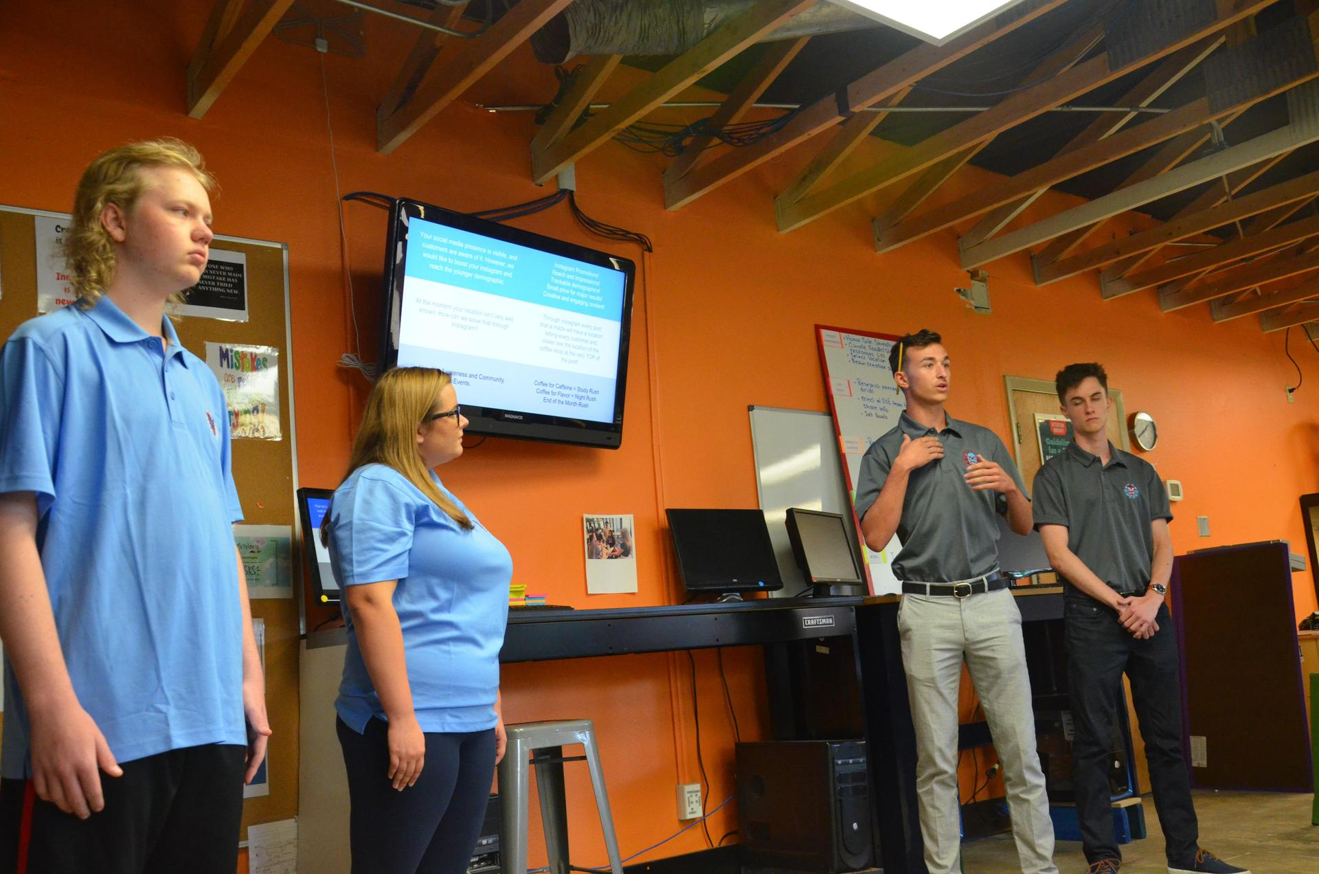 Four upper school students present their project to the class